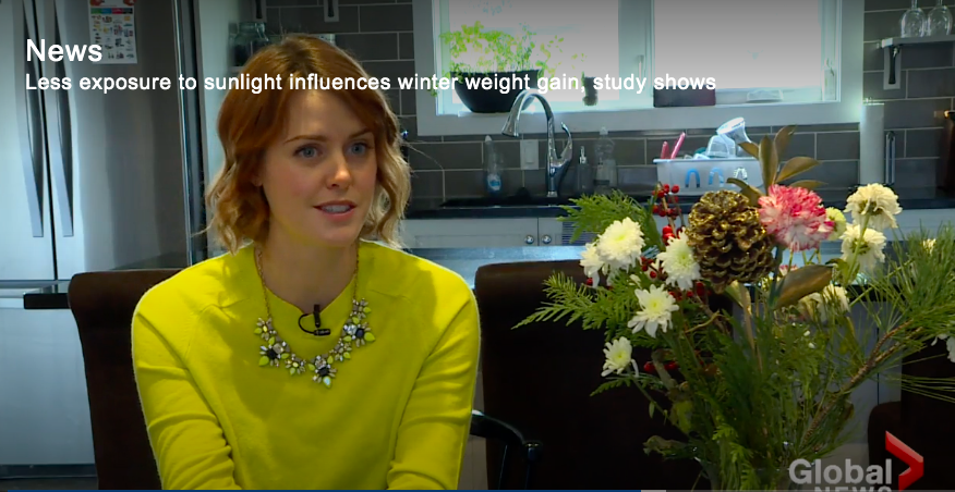 Dietitian Kerry Miller wearing a yellow sweater and sitting in her kitchen talking to a reporter