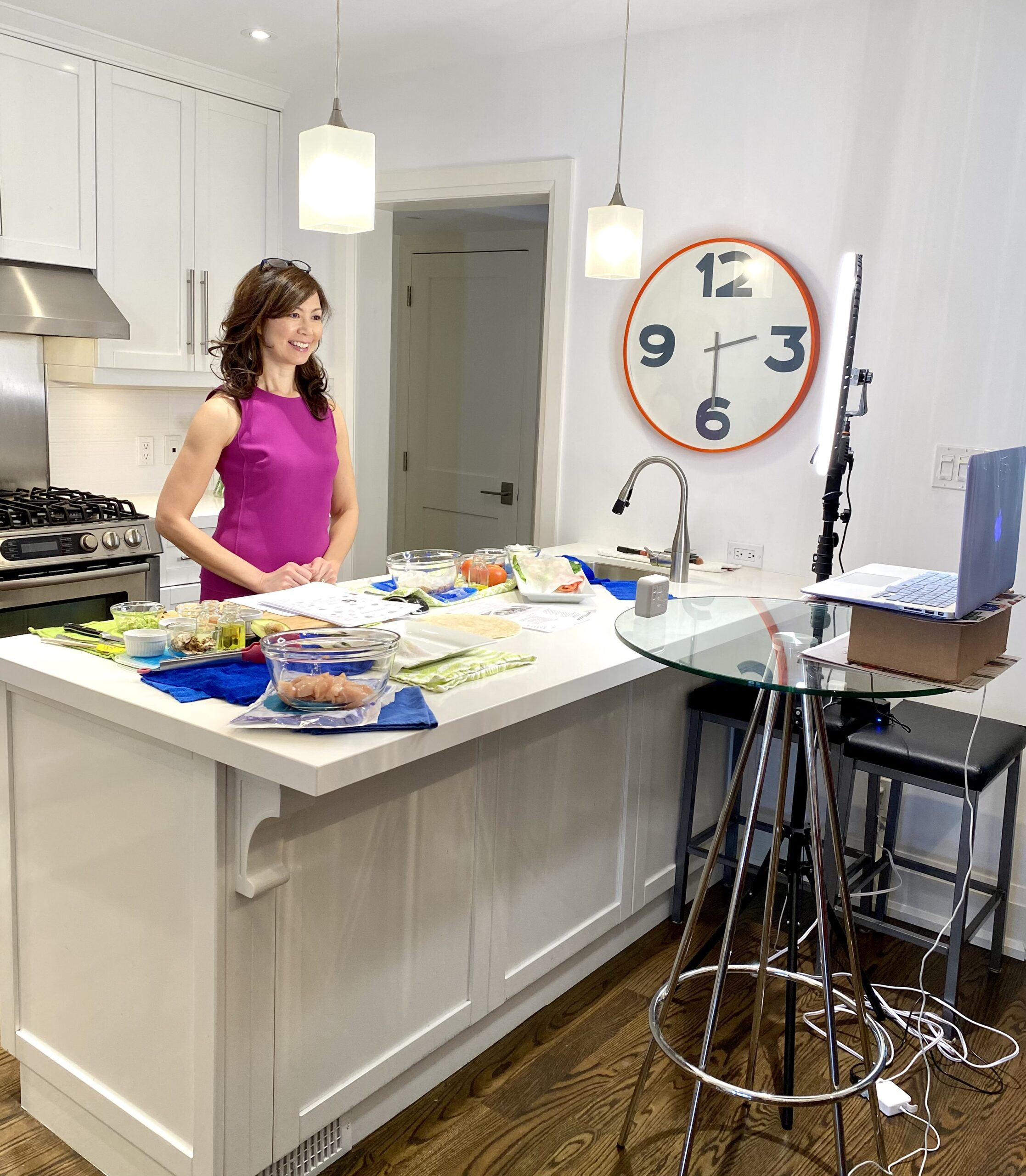 Sue is wearing a pink sleeveless dress and standing behind her white kitchen counter. She is looking at the laptop camera. On the counter are ingredients in glass bowls, veggies covered with a damp towel and a bowl of raw chicken placed on an ice-pak.