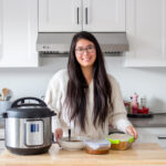 Carmy Do standing in her kitchen beside an Instant Pot