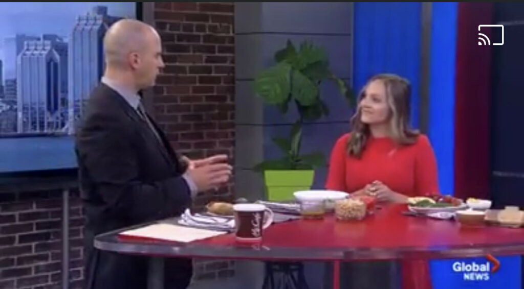 Hannah Magee in a TV studio and talking to a TV host.
