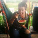 Chef Jillian Hillier sitting on a hammock and eating watermelon