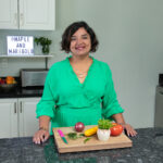 Puneeta wearing a green top and standing behind her kitchen counter with various food items on a cutting board.